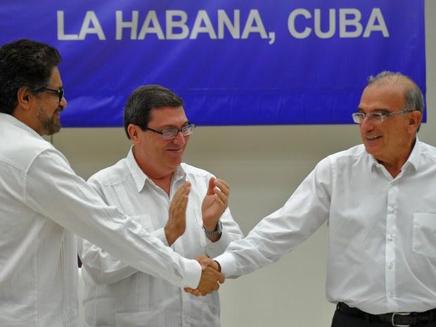 O comandante das Farc Iván Marquéz (esquerda) e o chefe da delegação de paz colombiana Humberto de la Calle (direita) apertam as mãos nesta quarta-feira (24) em Havana, Cuba, após assinarem o acordo definitivo de paz na Colômbia (Foto: YAMIL LAGE / AFP)