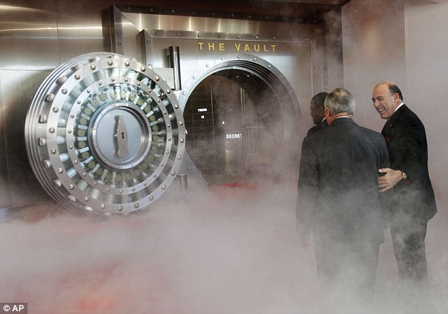 Smoke and mirrors? Georgia Governor Nathan Deal (centre) and Atlanta Mayor Kasim Reed (left) are led into the exhibit by Coca Cola chief Muhtar Kent - but is the formula the real thing?