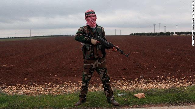 """Um membro da Brigada oposição síria Al-Buraq fica de guarda em uma rua principal no norte da cidade síria de Ain Dakna perto da fronteira com a Turquia na segunda-feira 10 de dezembro. Clique para ver as imagens através da luta a partir de dezembro, ou <a href = 'http://www.cnn.com/2012/12/04/middleeast/gallery/syria-unrest-november/index.html' target = ' _blank """"> veja fotos do conflito a partir de Novembro </ a>."""