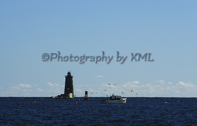 old stone lighthouse with a lobster boat