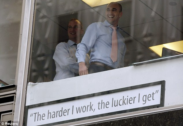 Gloating: Businessmen in a window laugh after placing a sign on their window above where Occupy Wall Street protesters were marching. It reads: 'The harder I work, the luckier I get'