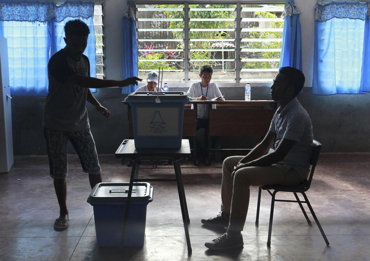 A man casts his ballot as an electoral worker, left, looks on during the presidential election at a polling station in Dili, East Timor, Monday, March 20, 2017. East Timorese went to vote Monday in the first presidential election since the U.N. officially ended the peacekeeping mission in the country in 2012.