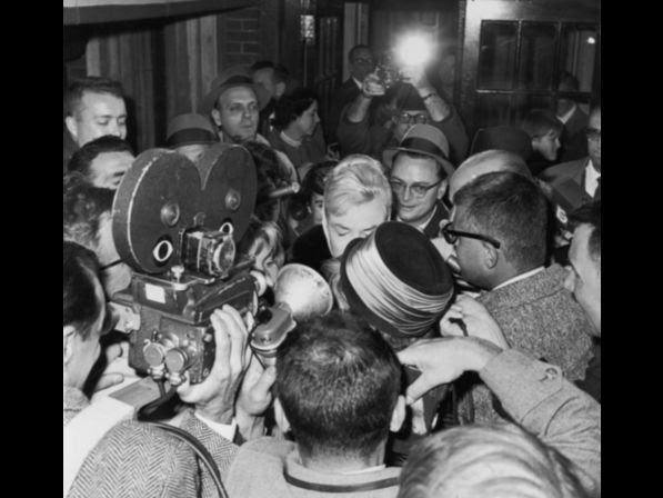 Monroe is surrounded by reporters and photographers as she leaves her apartment, shortly after announcing her divorce from Arthur Miller in 1960.
