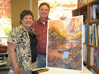 Roland Lee and Joan Stackpole in the studio with Roland Lee original painting of Zion national Park