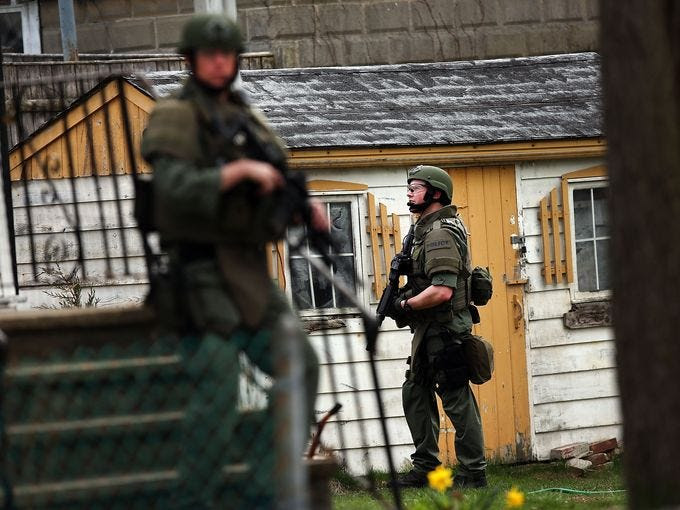Police search a Watertown, Mass., neighborhood for 19-year-old bombing suspect Dzhokhar Tsarnaev on April 19.