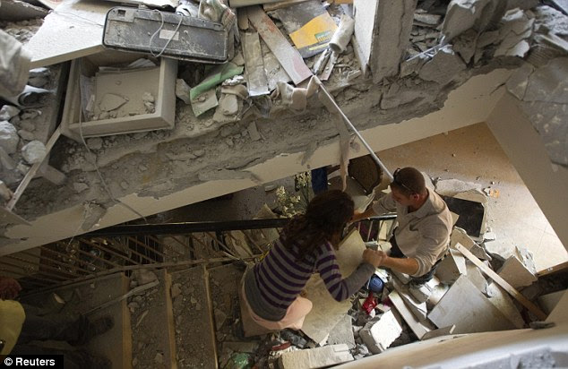 Damaged: Israelis survey the damage after a rocket hit their house in the southern city of Beersheba. The U.N. chief called for an immediate ceasefire in the Gaza Strip today