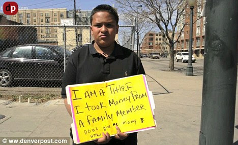 Humiliation: Jose Gonzales has to stand carrying this sign on a street corner after his father caught him stealing $100 from his cousin