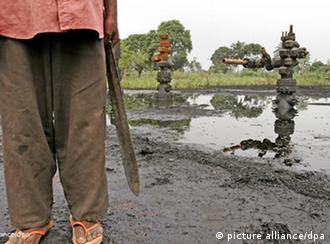 Jan 26, 2005; Ogoni, Rivers State, NIGERIA; K-Dere Community; Farmer Bakpa Birabil stands in front of two leaking oil wells on his farm, which has been owned by his family for centuries. The oil well (on his property) has been leaking for the past year without attention from Shell. Multinational oil companies, including Shell Oil (the biggest oil company in the Niger River Delta) have drawn attention because of poor business practices and inability to work with local communities. Tension between Nigerians living in the area, the Nigerian government and the oil production industry has made the Niger River Delta one of the most dangerous and volatile places on earth to conduct business. Mandatory Credit: Photo by Mark Allen Johnson/ZPress +++(c) dpa - Report+++