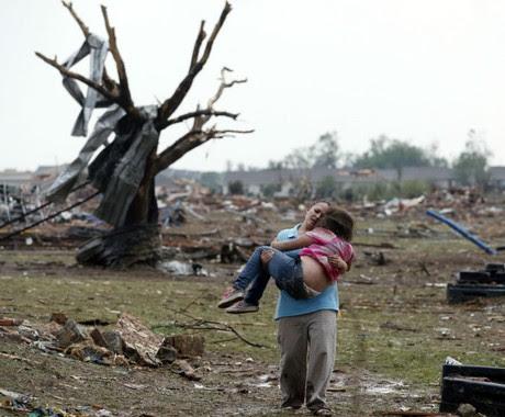 Uma mulher carrega sua criança por uma área perto da escola Plaza Towers, destruída pelo tornado em Moore, Oklahoma (Foto: Sue Ogrocki/AP)