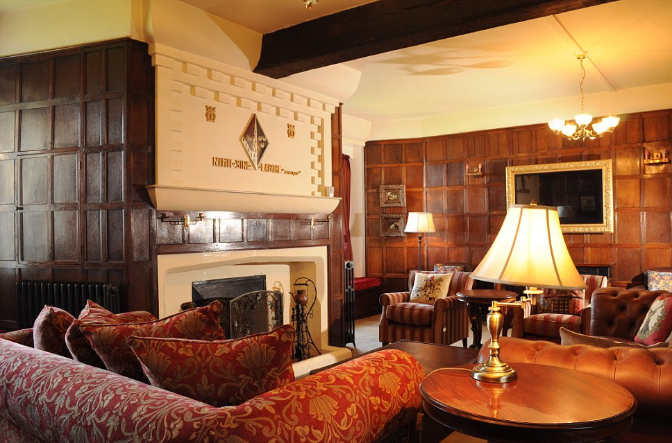 The drawing room at Happisburgh Manor features a fire and a coat of arms. There is also a huge mirror and plenty of comfortable chairs