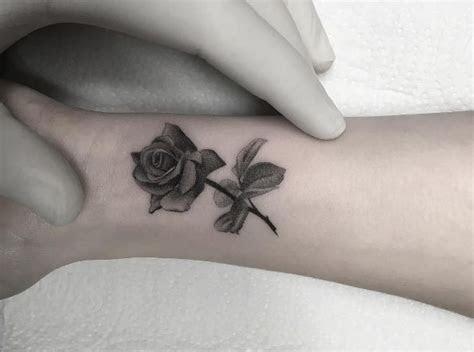 dark grey small rose tattoo wrist