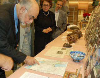Iranian diplomat looks at map, showing sites of past collaborative botanizing