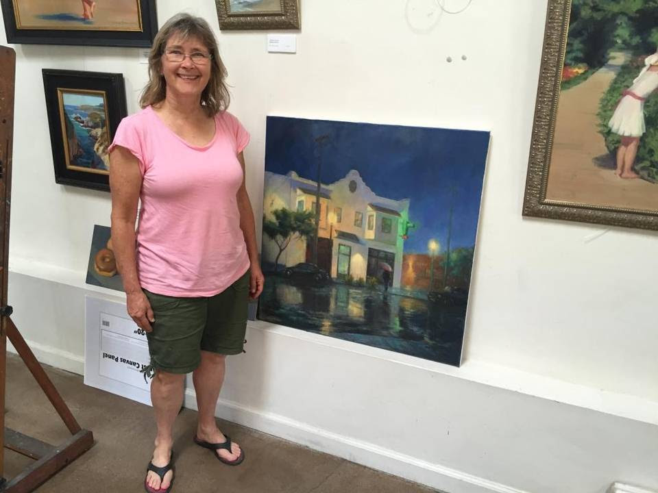 Patti Miller, better known as Patris Miller, stands by one of her paintings in her studio in Oak Park.
