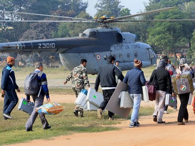 Polling personnel carry polling equipments at a helipad on the eve of the third phase of Jharkhand Assembly Election. PTI