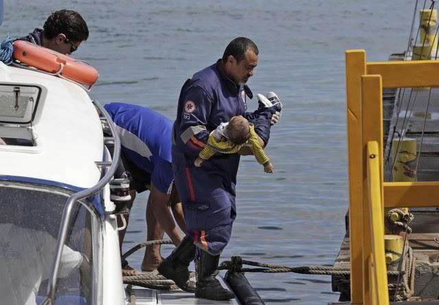 Socorrista do Samu leva um bebê no colo após uma embarcação naufragar em Mar Grande, na Baía de Todos os Santos, na Bahia (Foto: Xando Pereira/Agência A Tarde/Estadão Conteúdo