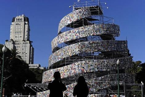 Dos personas observan la torre de libros en la plaza San Martín de Buenos Aires. | AFP