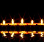 picture of condolence  - row of candles reflected in the water - JPG