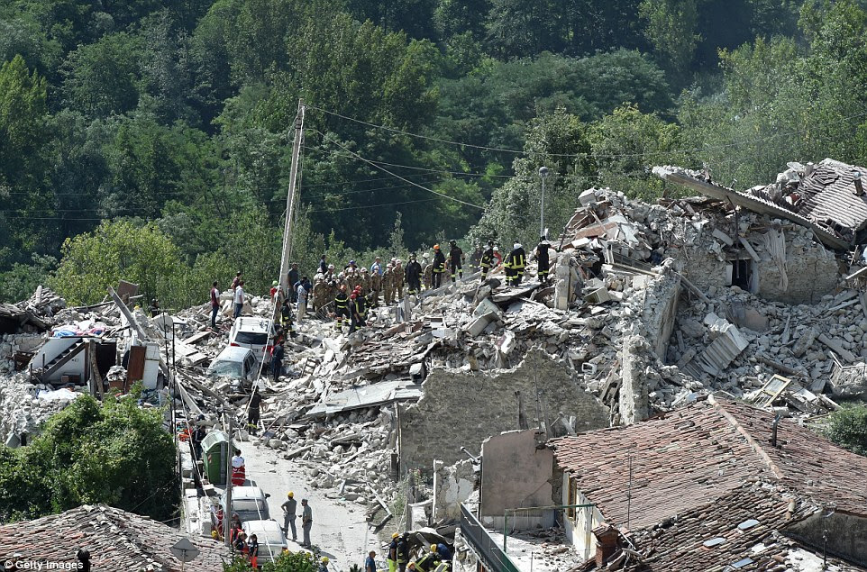 Apocalyptic: Streams of rescue workers climb the rubble in Pescara del Tronto as they desperately seek survivors