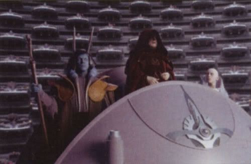 Darth Sidious, dressed in his Chancellor robe, addresses the Galactic Senate.
