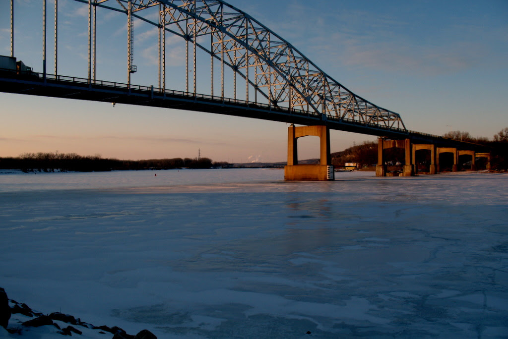 A view of the Hastings River bridge crossing over the frozen Mississippi River during the winter months.