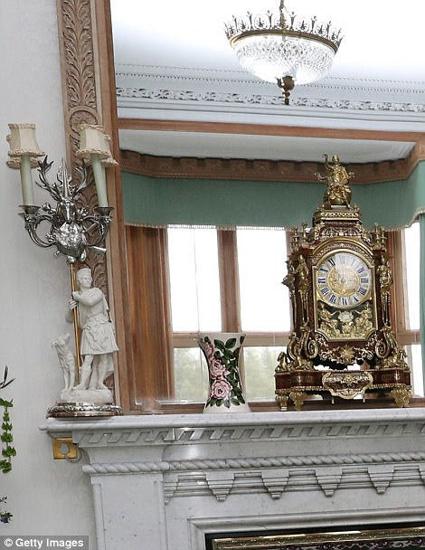 Frozen in time: The candlestick holders and the ornate gold clock on the mantelpiece today