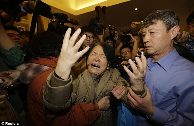 A hysterical family member of a passenger aboard MH370 reacts to the news of her loved one's death