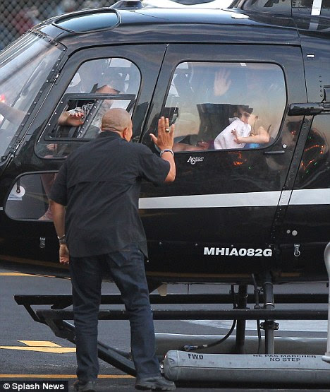 That's better: After her blanket is found by a member of staff Suri is seen waving thank you as the helicopter sets off