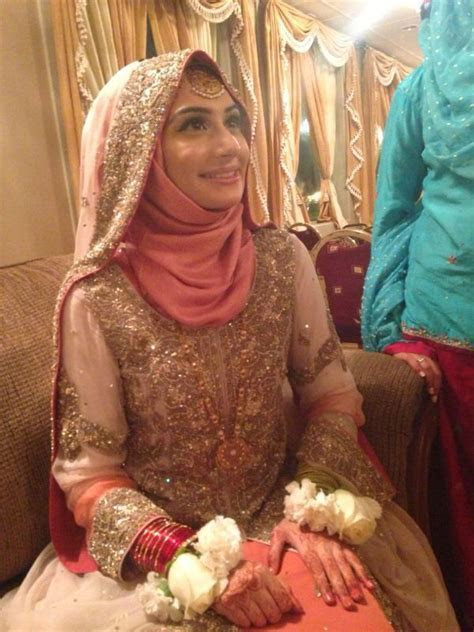 Bride in hijab wearing coral link and cream white. Makeup