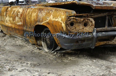 a rusty old car in the junkyard