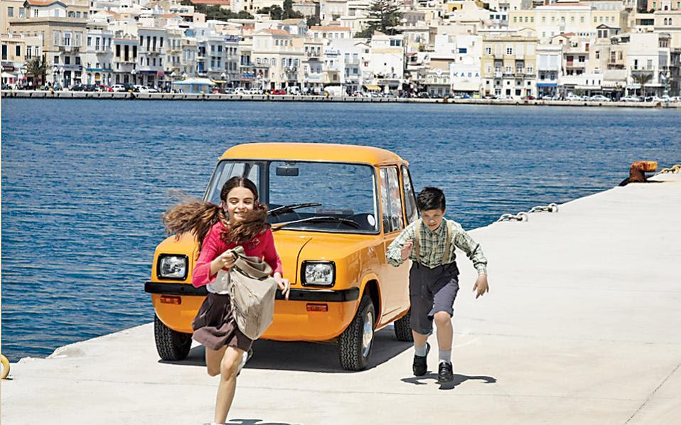 Το πορτοκαλί αυτοκίνητο στην προκυμαία της Σύρου είναι το πρώτο ηλεκτροκίνητο, παγκοσμίως, το οποίο κατασκευάστηκε στο νησί τη δεκαετία του '70! Εκατόν είκοσι οχήματα όλα κι όλα παρήγαγε το εργοστάσιο Enfield Automotive, ιδιοκτησίας Γιάννη Γουλανδρή, το οποίο μετεγκαταστάθηκε στα τέλη του '60 από το νησί Γουάιτ της Βρετανίας στη Σύρο, σ' ένα παλιό κλωστήριο κοντά στο Νεώριο. Την άγνωστη ιστορία του εντυπωσιακού ελληνικού εγχειρήματος αφηγείται το ντοκιμαντέρ «Ανάμεσα σε δύο νησιά» του Μιχάλη Σταυρόπουλου, το οποίο θα προβληθεί σε λίγες ημέρες στο 16ο Φεστιβάλ Ντοκιμαντέρ στη Θεσσαλονίκη.