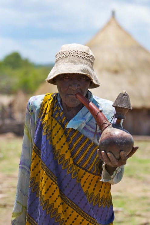Old Tonga woman smoking water pipe, near Binga, Zimbabwe