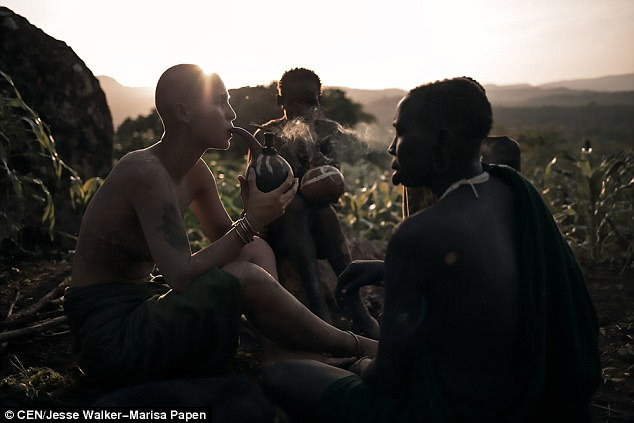 Papen smokes using a traditional tribal pipe with the member of the Surma during her trip