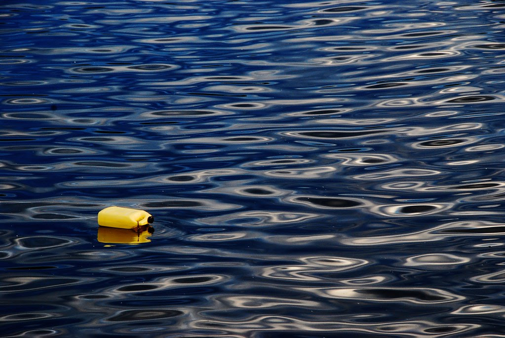 A yellow bottle floating on blue water.