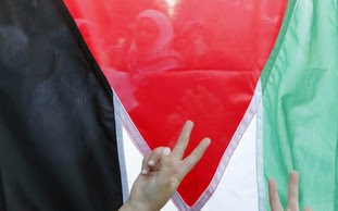 Victory signs flashed in front of Palestinian flag