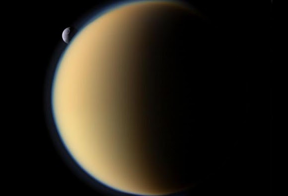 Saturn's moon Titan with Tethys hovering in the background. Image taken by the Cassini spacecraft. Credit: NASA/JPL/Space Science Institute
