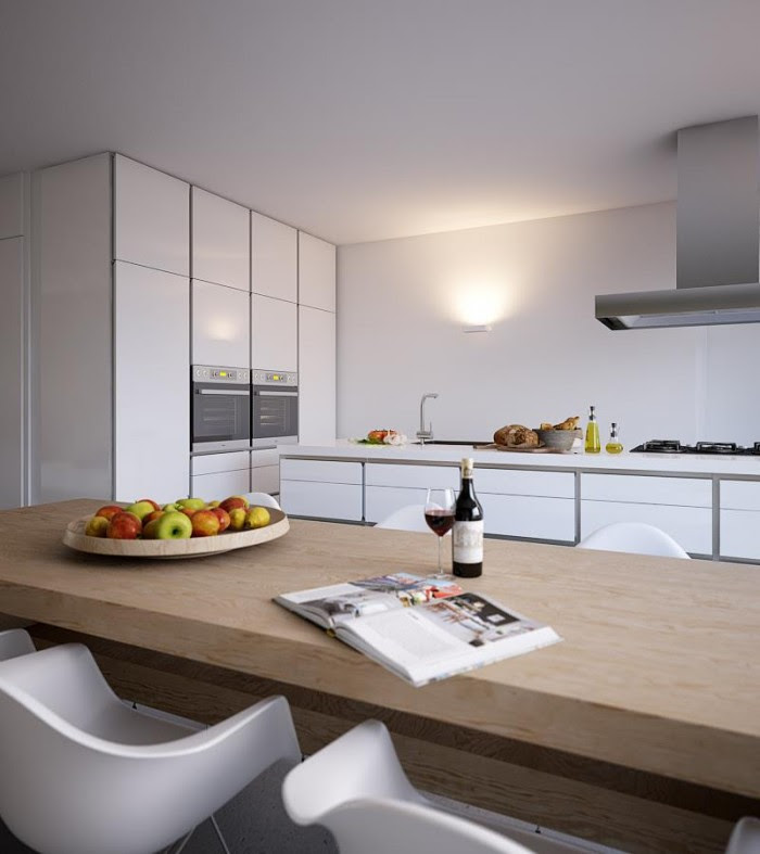The faces of the kitchen cabinets are glossy white, which bounces the natural light around the area, but are defined perfectly by gray framing that help tie in the tone of the feature wall.