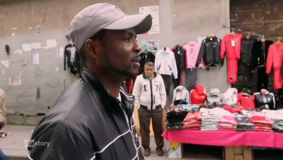 Ein junger dunkelhäutiger Mann geht durch die Straße im Hintergrund stehen Kleidung-Straßenständer.