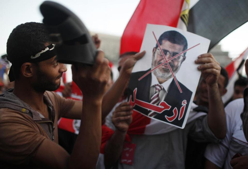 A protester used his sandal to beat a crossed-out picture of Egypt's Islamist President Mohammed Morsi in Cairo.