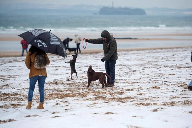Varias personas caminan sobre la nieve en la segunda playa del Sardinero
