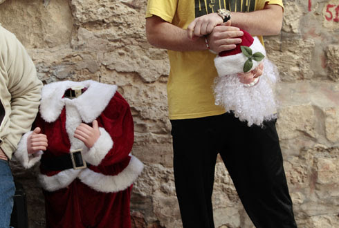 Reuters photos, Baz Ratner - A vendor holds the head of a Santa Claus doll as he arranges a display outside a shop in Jerusalem's Old City (December 21, 2010)