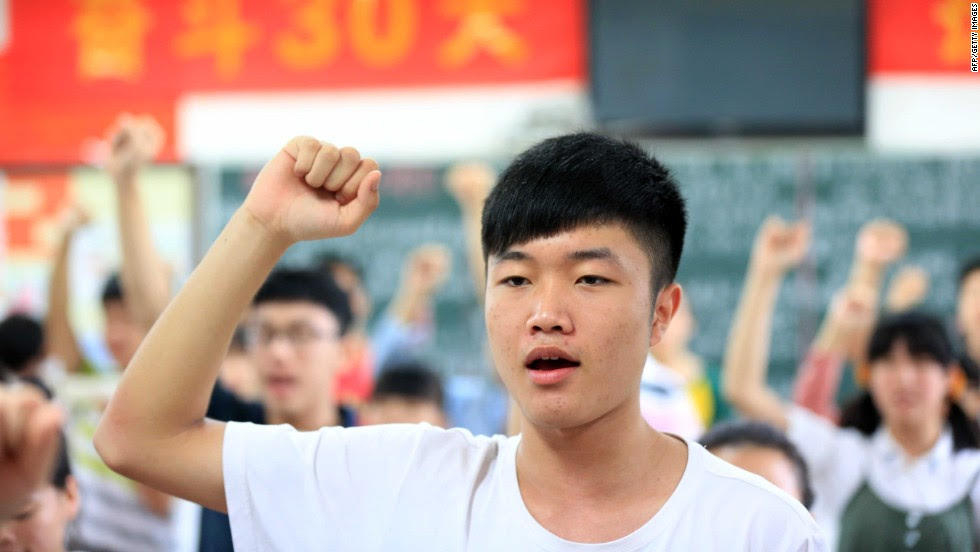 "Students vow to obey the exam regulations before sitting the 2014 college entrance exam of China, or the ""gaokao,"" in Bozhou, east China's Anhui province. Nearly 10 million high school students sat for China's make-or-break college entrance exams under tight security this year."