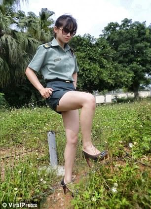 The photos show the young woman wearing sunglasses, high heels and the green Taiwanese military uniform - a tight short-sleeved shirt and a mini skirt - and posing for the shots
