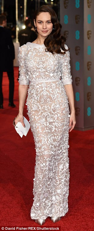 Sheer bliss: Former Bond girlOlga Kurylenko made sure to make an impact in her beautiful, delicately covered sheer dress by Ralph & Russowith a white lace pattern as she arrived with the other stars