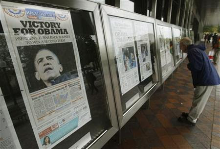People view various newspaper front pages showing President Barack Obama's victory over Republican presidential candidate Mitt Romney on display at the Newseum in Washington November 7, 2012. REUTERS/Gary Cameron