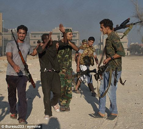 Racism? Rebel fighters hold captive a sub-Saharan African man suspected of working as a mercenary for the Gaddafi regime last August