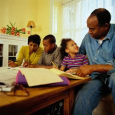 Photograph of parents helping their two children with homework