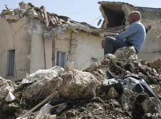 Man sitzt auf Trümmern Trümmern vor einem Haus in der Ortschaft Onna (Foto: AP)