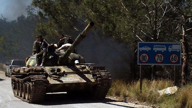 A picture taken on March 31, 2014 and released by the official Syrian Arab News Agency on April 3, 2014 allegedly shows pro-government forces sitting on a tank at an undisclosed location in the north of Syria's Latakia province