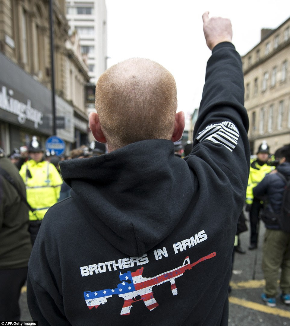 This man raised his hand in a defiant gesture with his hooded top featuring an AR15 assault rifle covered in an American flag