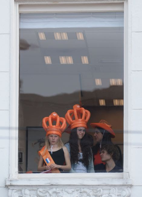 People wear inflatable crowns as they gather in an office building on Dam Square